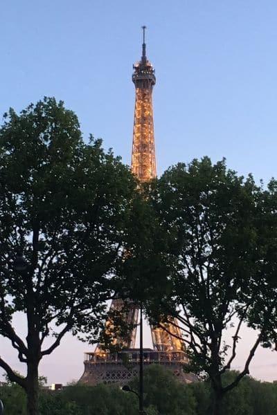 Eiffel Tower lit through the trees Paris