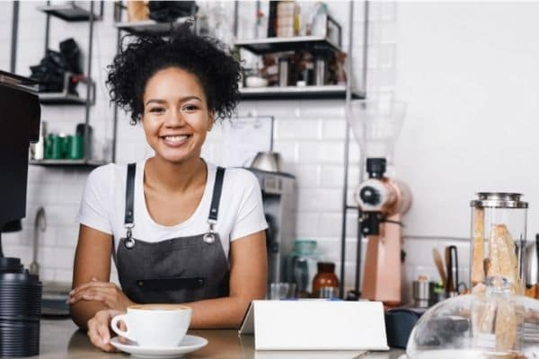 Female barista working 2nd job to save money for travel