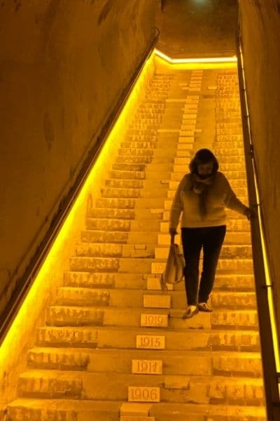 Woman walking down stairs to enter Veuve Clicquot cavern