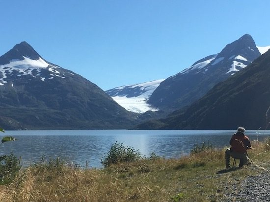 Man taking pictures of Portage ice shelf Alaska