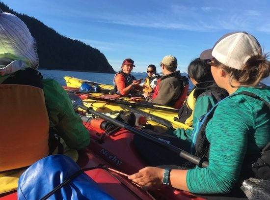 Kayaker guide with kayakers on water in Alaska