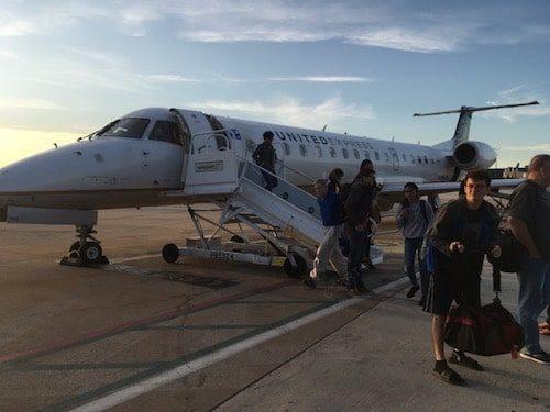 People disembarking airplane on tarmac during travel