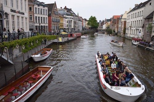 People in boat on river Ghent Belgium, a solo travel destination