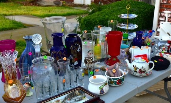Home items on yard sale table are a great way to save money for travel