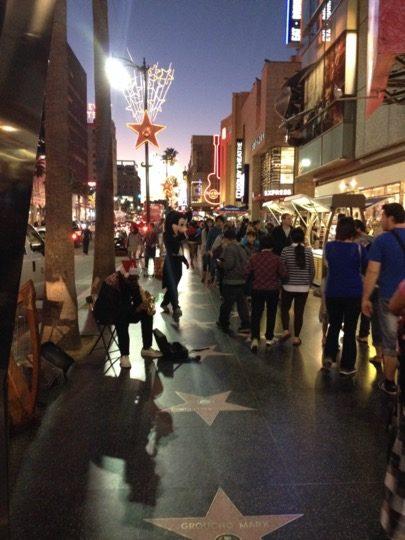 People walking on Hollywood Blvd at dusk