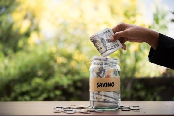 Person putting money in savings jar to save money for travel