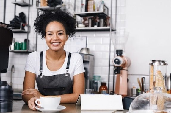 Woman barista behind counter