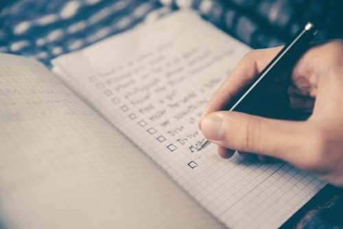 Image of person checking off checklist for your first solo trip